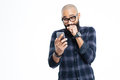 Cheerful african american bald man using smartphone and laughing Royalty Free Stock Photo
