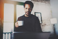 Cheerful African man using computer and smiling at the living room.Black guy holding ceramic cup in hand.Concept of Royalty Free Stock Photo