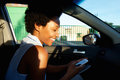 Cheerful african woman using mobile phone in a car