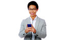 Cheerful asian man using smartphone over white background Royalty Free Stock Photo