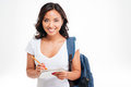 Cheerful attractive asian girl with backpack making notes in notebook Royalty Free Stock Photo