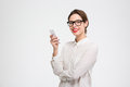 Cheerful attractive businesswoman in glasses standing and using mobile phone Royalty Free Stock Photo