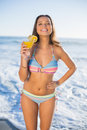 Cheerful attractive woman in bikini holding cocktail on the beach on a sunny day Stock Photos