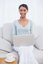 Cheerful attractive woman using her laptop sitting on cosy sofa in bright living room Stock Photo