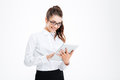 Cheerful attractive young businesswoman in glasses standing and using tablet Royalty Free Stock Photo