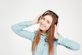 Cheerful attractive young woman in headphones listening to music over white background Stock Photography