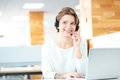 Cheerful attractive young woman working with headset and laptop sitting in call center in office Royalty Free Stock Image