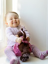 Cheerful baby girl plays with toy bear Royalty Free Stock Photo