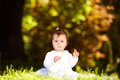 Cheerful baby girl sitting on the green grass in the city park at summer day. Royalty Free Stock Photo