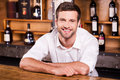 Cheerful bartender handsome young male in white shirt leaning at the bar counter and smiling Stock Photos