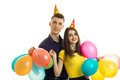 Cheerful beautiful couple celebrating birthday laughing and holding many balls