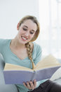 Cheerful beautiful woman reading a book while sitting on couch in the living room Royalty Free Stock Photos