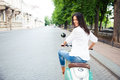 Cheerful beautiful woman riding a scooter young and looking back at camera Stock Images