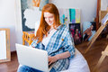 Cheerful beautiful woman sitting on soft beanbag and using laptop
