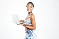 Cheerful beautiful young african american sportswoman standing and using laptop Royalty Free Stock Photo