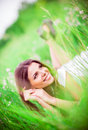 Cheerful beautiful young woman lying among grass and flowers