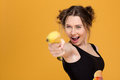 Cheerful beautiful young woman pointing with banana on you over yellow background Royalty Free Stock Photos