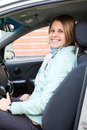 Cheerful blond female driver in car Stock Photo