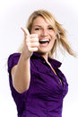 Cheerful blond woman showing thumbs up beautiful an open smile and a wearing a purple shirt on a white background Royalty Free Stock Photos