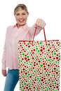 Cheerful blonde girl holding shopping bag in outstretched arm Royalty Free Stock Image