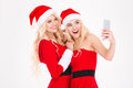 Cheerful blonde sisters twins making selfie using cell phone Royalty Free Stock Photo