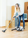 Cheerful blonde woman in headphones with vacuum cleaner cleaning on parquet floor Royalty Free Stock Photography