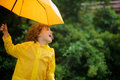 Cheerful boy with a bright yellow umbrella in raincoat laddie protrude tongue and catches rain drops he is amused by such game Stock Photo