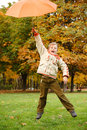 Cheerful boy in park. Has jumped with umbrella Stock Images