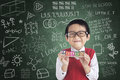 Cheerful boy student holding learn block toy in front of written board Royalty Free Stock Photo