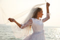 Cheerful bride near water sparkling holding her flying veil Royalty Free Stock Photo