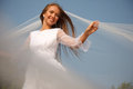 Cheerful bride young is holding her flying veil selective focus Stock Photo