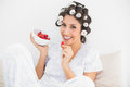 Cheerful brunette in hair rollers having a bowl of strawberries at home bedroom Royalty Free Stock Photography