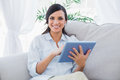 Cheerful brunette with tablet pc in living room Royalty Free Stock Photography