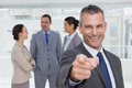 Cheerful businesman pointing at camera with colleagues on backgr in bright office background Stock Image