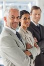 Cheerful business people looking in the same way with their arms crossed Royalty Free Stock Photography