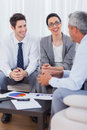 Cheerful business people talking and working together on sofa at office Stock Photography
