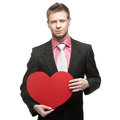Young surprised businessman holding red heart