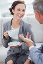 Cheerful businesswoman having coffee with her workmate in bright office Royalty Free Stock Photos