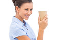 Cheerful businesswoman holding a coffee cup and looking away Stock Photos