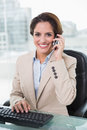 Cheerful businesswoman phoning and looking at camera in bright office Royalty Free Stock Image