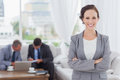 Cheerful businesswoman posing while her colleagues are working in bright office Royalty Free Stock Image