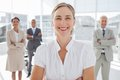Cheerful businesswoman standing with arms folded in front of colleagues Stock Images