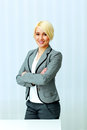 Cheerful businesswoman standing with arms folded young at office Royalty Free Stock Photography
