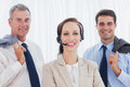Cheerful call center agent posing with her work team in bright office Stock Image
