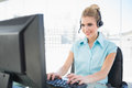 Cheerful call centre agent working on computer in bright office Royalty Free Stock Photo