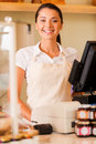 Cheerful cashier beautiful young female in apron standing near cash register and smiling Royalty Free Stock Photography