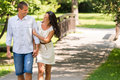 Cheerful caucasian couple walking outdoors hand in hand Stock Photos