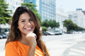 Cheerful caucasian woman in a orange shirt in the city Royalty Free Stock Photo