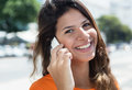 Cheerful caucasian woman in a orange shirt at phone Royalty Free Stock Photo