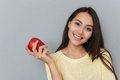 Cheerful charming young woman holding red apple Royalty Free Stock Photo